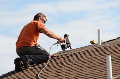 Man Working on Roof with Screwdriver